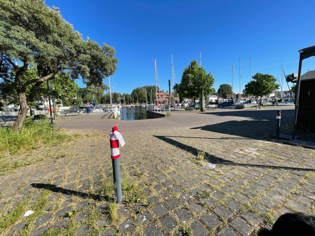 Im Vordergrund ein Poller mit einer rotweiß geringelten Pollermütze. Im Hintergrund einige Häuser und die Slipanlage am Hafen des Ortsteils Wieck